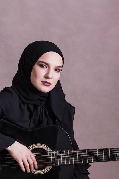 Retrato, de, mulher árabe, com, guitarra Foto gratuita