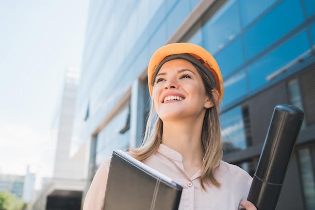 Retrato de mulher arquiteto profissional usando capacete amarelo e em pé ao ar livre. conceito de engenheiro e arquiteto. Foto gratuita