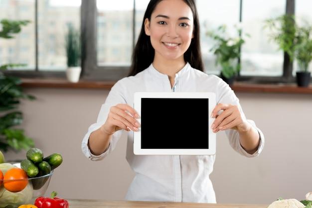 Retrato, de, mulher asian, mostrando, tela em branco, tablete digital, em, cozinha Foto gratuita