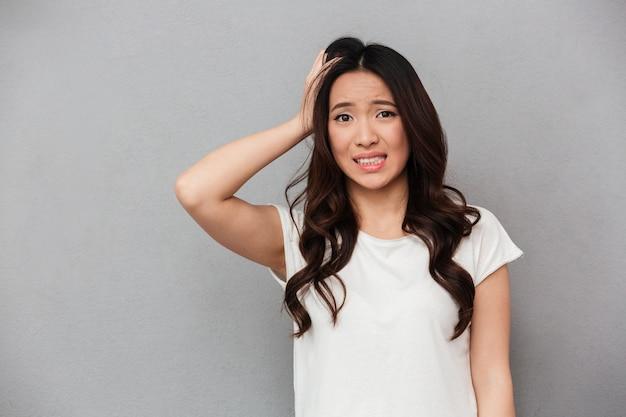 Retrato de mulher asiática 20 anos com cabelo escuro encaracolado, tocando sua cabeça e expressando preocupação isolada, sobre parede cinza Foto Premium