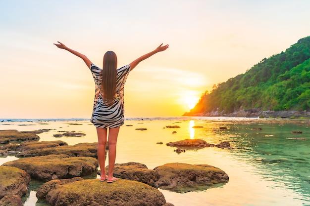 Retrato de mulher asiática na rocha com os braços abertos ao pôr do sol ao redor do oceano nas férias Foto gratuita