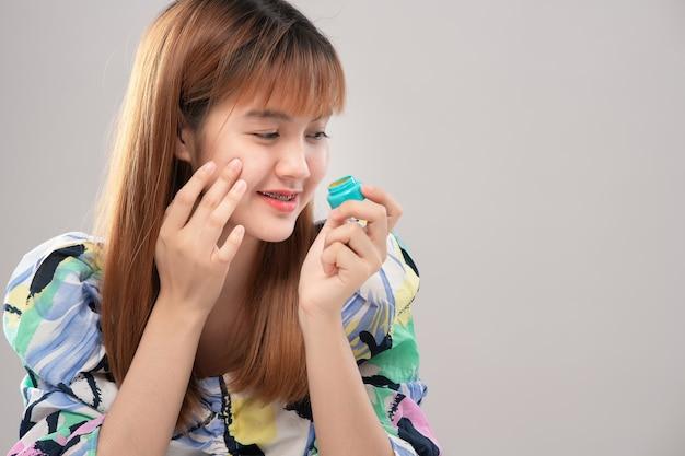 Retrato de mulher bonita asiática, apresentando creme para o rosto; perfeição rejuvenescimento revitalização hidratante e conceito de cuidados com a pele. modelo mostrando o produto de beleza na mão Foto Premium