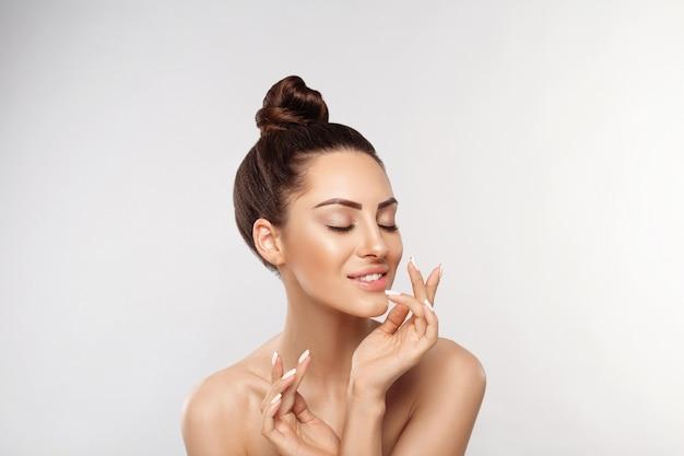 Retrato de mulher bonita, conceito de cuidados com a pele, cuidados com a pele. dermatologia. retrato de mãos femininas com unhas de manicure tocando seu rosto. Foto Premium