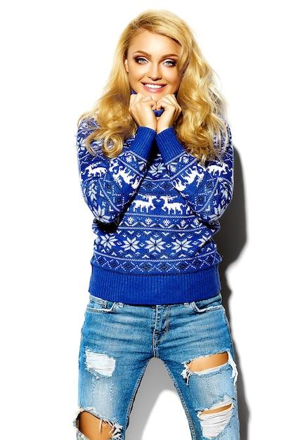 Retrato de mulher bonita feliz sorridente mulher loira doce em roupas de inverno quente casual hipster, em camisola azul com veados Foto gratuita