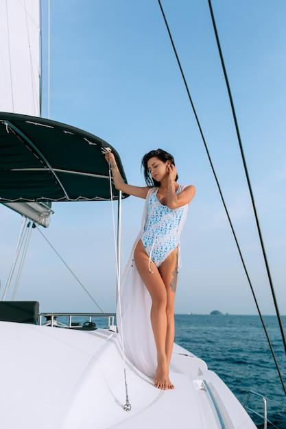 Retrato de mulher bonita moda jovem de pé e posando em veleiro ou iate no mar vestindo maiô branco moderno Foto Premium