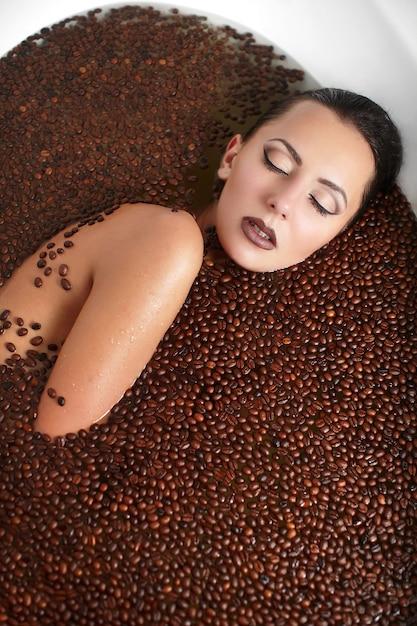 Retrato de mulher bonita moda na banheira de hidromassagem com café. cuidados com o corpo. maquiagem brilhante Foto gratuita
