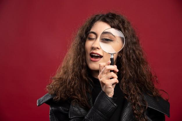 Retrato de mulher bonita, olhando através da lupa. Foto gratuita