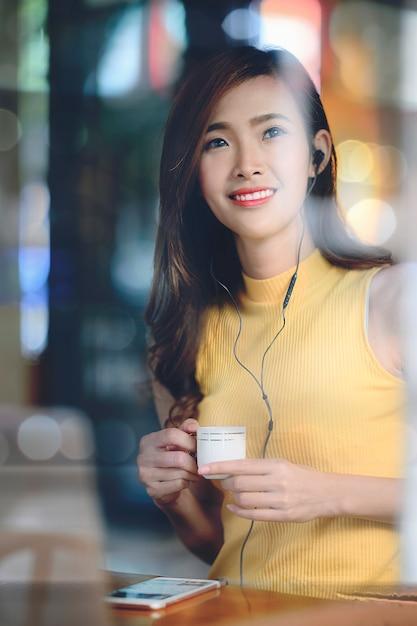 Retrato, de, mulher bonita, sentando, em, café, com, noturna, luz Foto Premium