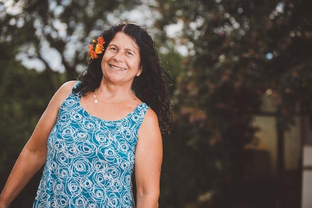 Retrato de mulher bonita sorridente na natureza com flores no cabelo Foto Premium
