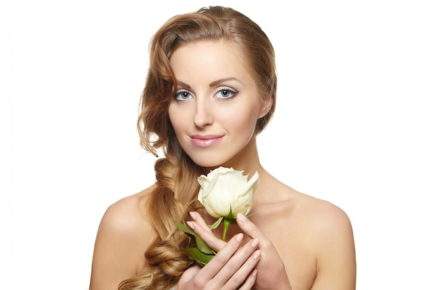 Retrato de mulher bonita sorridente sensual com rosa branca sobre fundo branco, cabelo encaracolado, maquiagem brilhante Foto gratuita