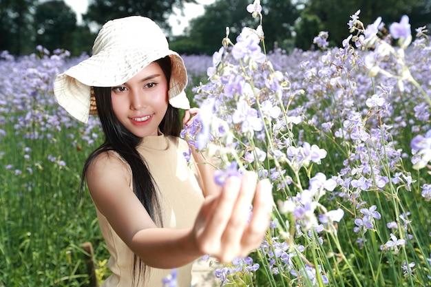 Retrato, de, mulher bonita, tendo, um, tempo feliz, e, desfrutando, entre, flor, naga-crested, campo, em, natureza Foto Premium