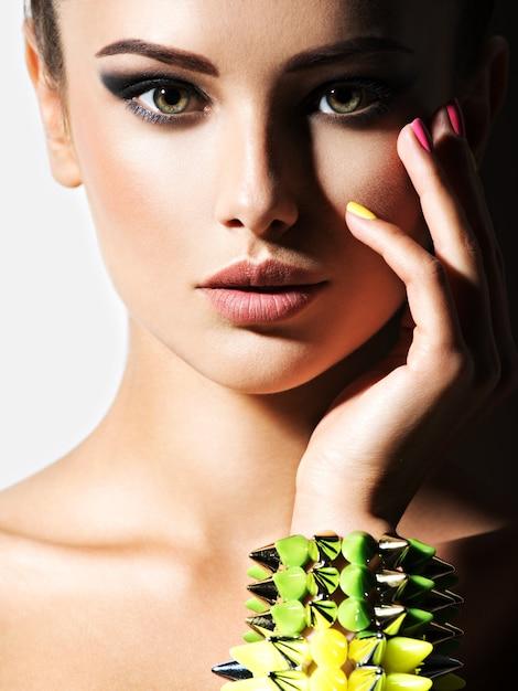 Retrato de mulher bonita usando pulseira com espinhos Foto gratuita