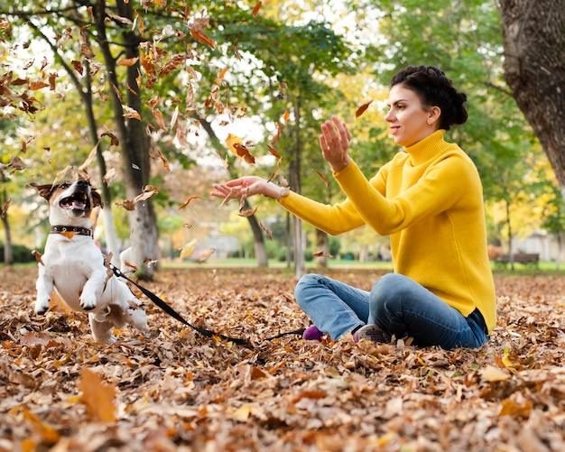Retrato de mulher brincando com seu cachorro no parque Foto gratuita