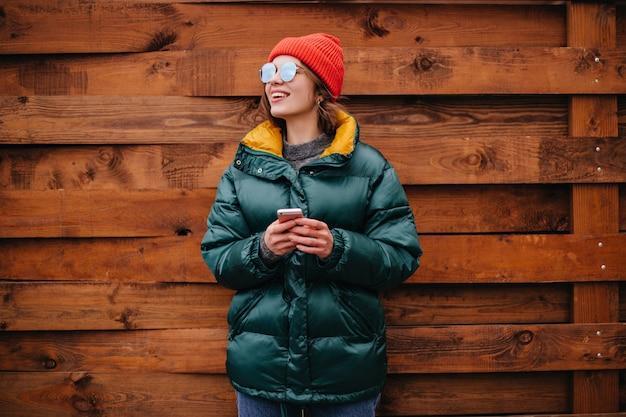 Retrato de mulher com casaco verde esmeralda na parede de madeira Foto gratuita
