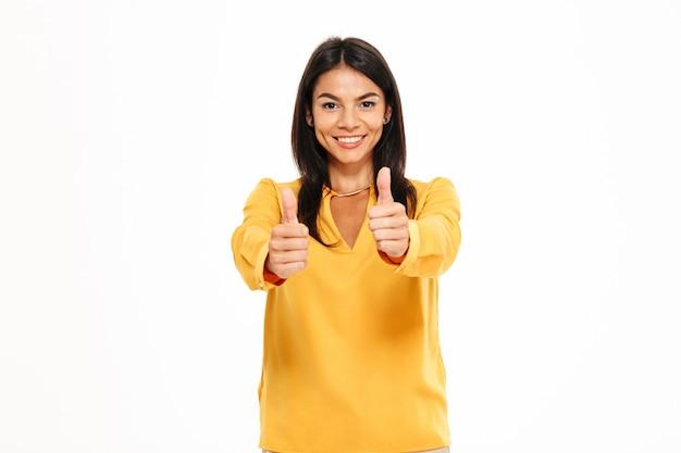 Retrato de mulher confiante feliz mostrando os polegares para cima gesto Foto gratuita