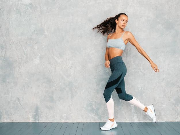 Retrato de mulher confiante fitness em roupas esportivas, olhando confiante. feminino posando no estúdio perto da parede cinza Foto gratuita
