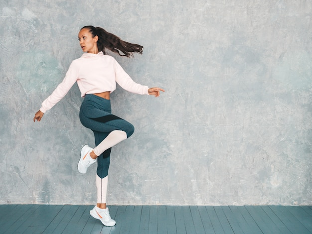 Retrato de mulher confiante fitness em roupas esportivas, olhando confiante. feminino pulando no estúdio perto da parede cinza Foto gratuita