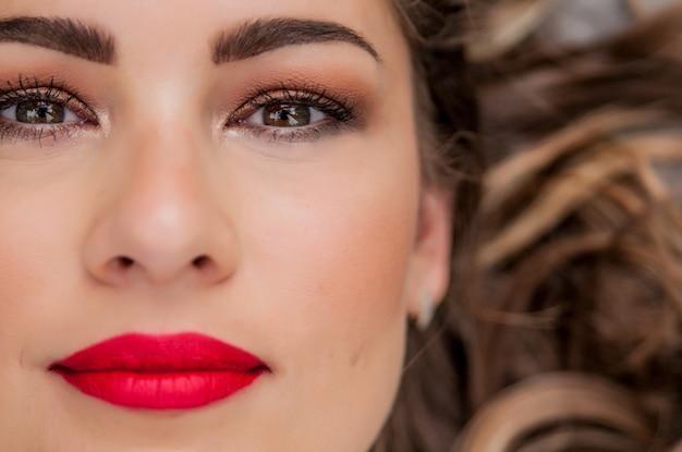 Retrato de mulher de beleza. maquiagem profissional para morena com olhos verdes - batom vermelho, olhos fracos. menina bonita do modelo de moda. pele perfeita. maquiagem. isolado em um fundo branco. parte do rosto Foto gratuita