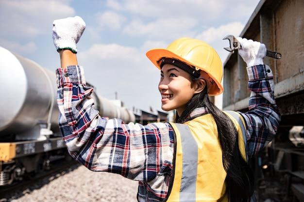Retrato de mulher de engenheiros trabalhando no local da garagem de trens e segurando a chave para reparos. Foto Premium