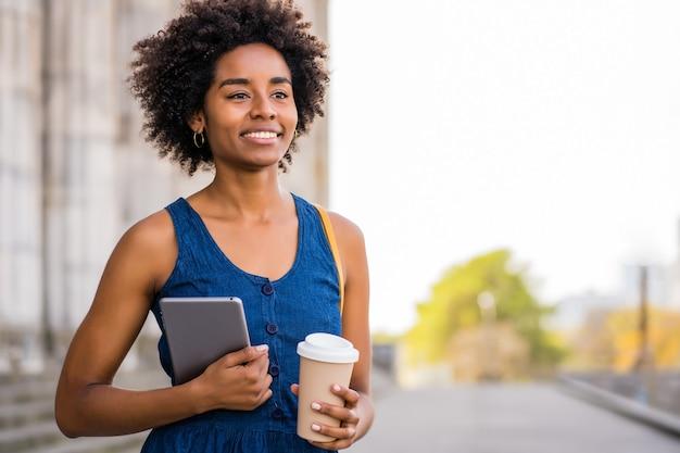Retrato de mulher de negócios afro segurando um tablet digital e uma xícara de café em pé ao ar livre na rua. negócios e conceito urbano. Foto gratuita