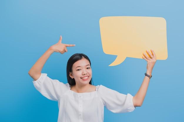 Retrato de mulher de negócios asiáticos linda confiante em pé e segurando o discurso de bolha amarela em branco. Foto Premium