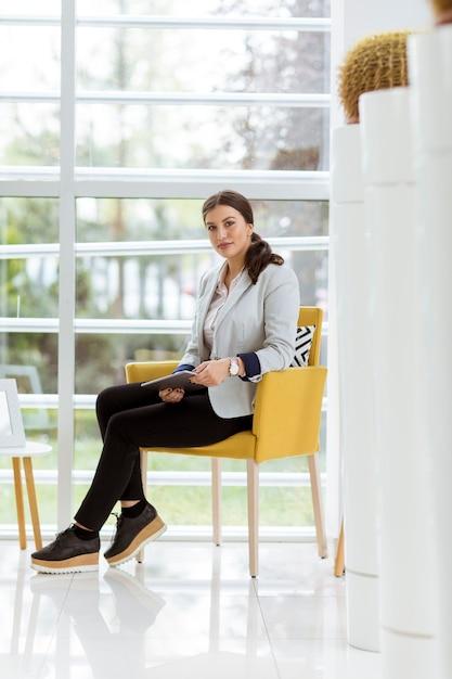 Retrato de mulher de negócios jovem atraente trabalhando on-line com um tablet digital Foto Premium