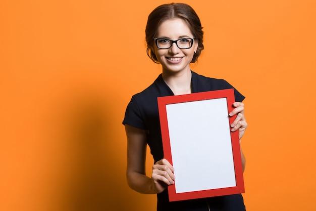 Retrato de mulher de negócios jovem bonita confiante segurando a moldura de foto em branco nas mãos dela Foto Premium