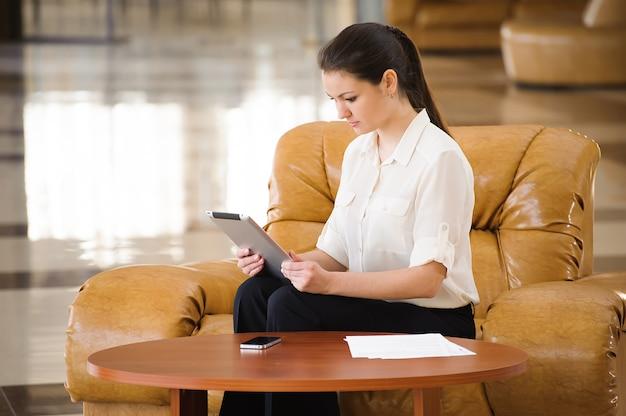Retrato de mulher de negócios ocupada trabalhando enquanto está sentado no sofá Foto Premium