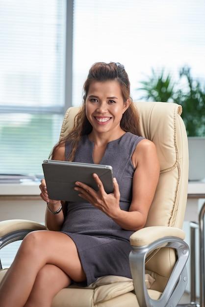 Retrato de mulher de negócios, trabalhando no computador tablet em sua cadeira de escritório Foto gratuita