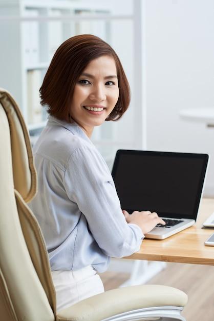 Retrato de mulher de negócios, voltando-se para olhar para a câmera com as mãos digitando no teclado na mesa do escritório Foto gratuita