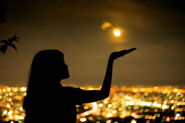 Retrato de mulher de silhueta com lua cheia na cidade à noite luz bokeh de fundo Foto Premium