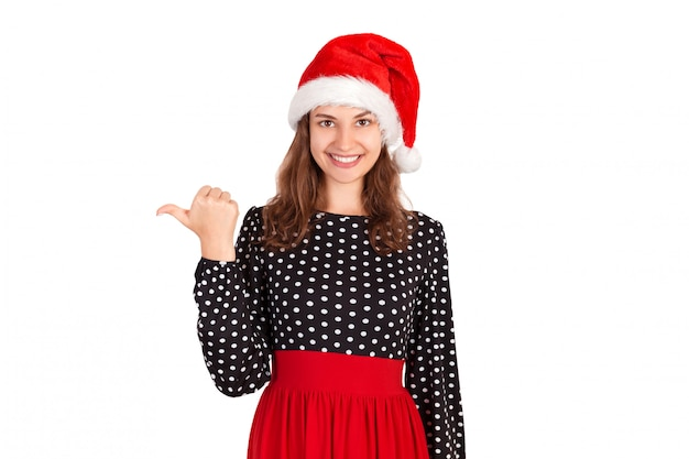 Retrato de mulher de vestido, apontando à esquerda com o polegar e sorrindo. garota emocional no chapéu de natal papai noel isolado Foto Premium