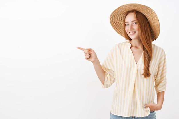 Retrato de mulher elegante ruiva feliz e feminina encantadora aproveitando o dia de verão na praia com chapéu de palha e blusa amarela da moda apontando para a esquerda Foto gratuita