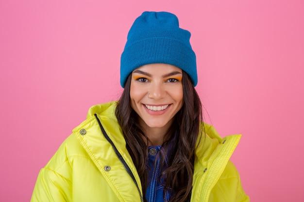 Retrato de mulher elegante sorridente atraente posando na parede rosa em inverno colorido casaco de cor amarela, usando chapéu de malha azul, vestido com roupas quentes, tendência da moda Foto gratuita