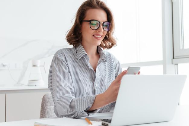 Retrato de mulher encantadora de óculos e camisa listrada, usando telefone celular enquanto localização no local de trabalho no quarto branco Foto gratuita