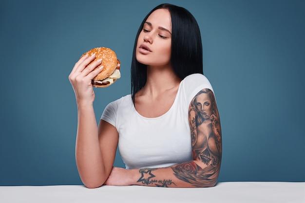 Retrato de mulher encantadora tatuagem segurando o hambúrguer Foto Premium