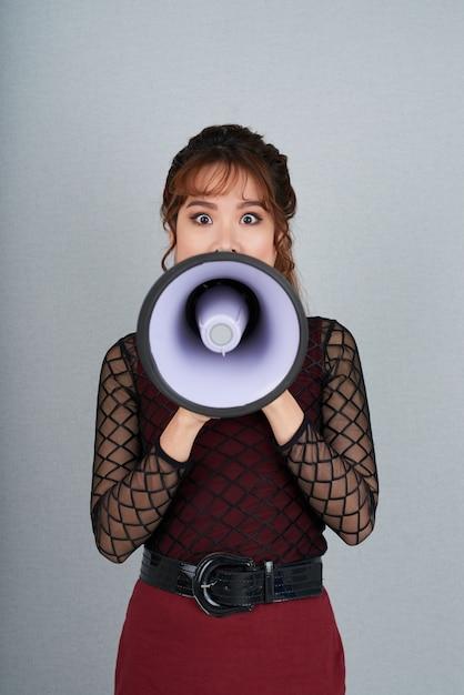 Retrato de mulher fazendo um anúncio através do alto-falante Foto gratuita