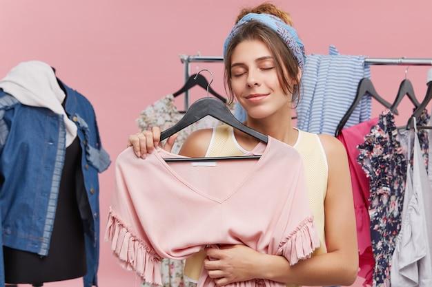 Retrato de mulher feliz em pé no provador, segurando o vestido elegante, fechando os olhos com prazer, sendo satisfeito com a nova compra. cliente feminino na loja de roupas, escolhendo o vestido para si Foto gratuita