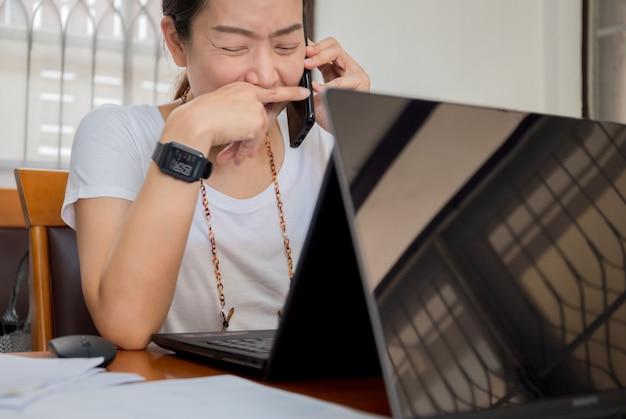 Retrato de mulher feliz falando no celular e trabalhando no laptop em casa. Foto Premium