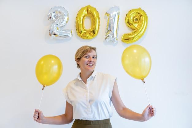 Retrato, de, mulher feliz, ficar, com, balões, sob, 2019, sinal Foto gratuita