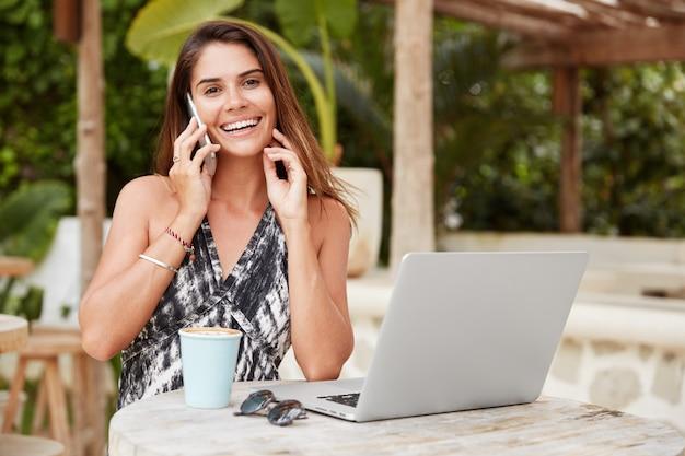 Retrato de mulher feliz lê as últimas notícias no site da internet, compartilha informações com um amigo próximo, usa aparelhos eletrônicos modernos para estar sempre em contato, recrie em um café na calçada Foto gratuita