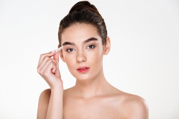 Retrato de mulher gentil bonita com pele limpa, depilando as sobrancelhas com pinça Foto gratuita