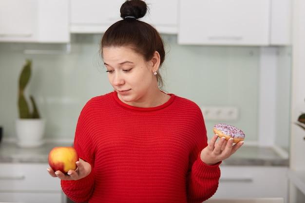 Retrato de mulher grávida decidir escolher alimentos saudáveis ou insalubres, posando no interior da cozinha branca Foto Premium