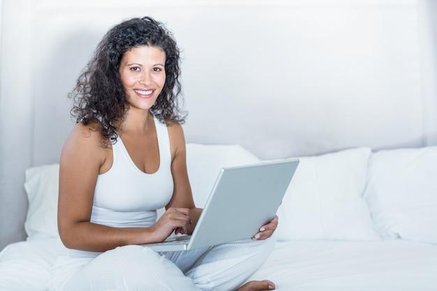 Retrato de mulher grávida linda usando laptop Foto Premium