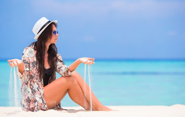 Retrato, de, mulher jovem, areia jogando, em, praia, durante, verão, férias Foto Premium