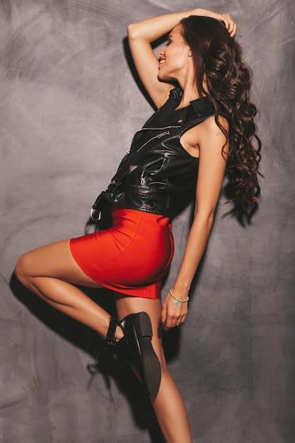 Retrato de mulher jovem bonita sorridente hipster na saia na moda verão vermelho e jaqueta de couro preta. mulher despreocupada sexy posando perto da parede. modelo moreno com maquiagem e penteado Foto gratuita