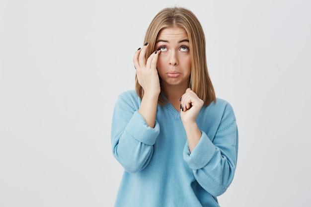 Retrato de mulher jovem caucasiano com rosto oval, olhos escuros e cabelos lisos, vestindo blusa azul casual, tocando seu rosto, tentando tirar a pestana dos olhos, olhando para cima. Foto gratuita