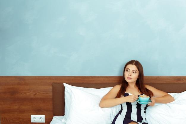 Retrato, de, mulher jovem, com, xícara café, ou, chá, cama Foto Premium