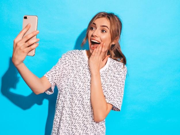 Retrato de mulher jovem e alegre tirando foto de selfie. linda garota segurando a câmera do smartphone. modelo de sorriso que levanta perto da parede azul no estúdio. modelo surpreso chocado Foto gratuita