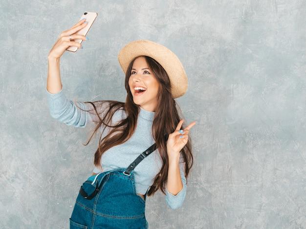 Retrato de mulher jovem e alegre tirando foto selfie e vestindo roupas e chapéu modernos. . mostra sinal de paz Foto gratuita